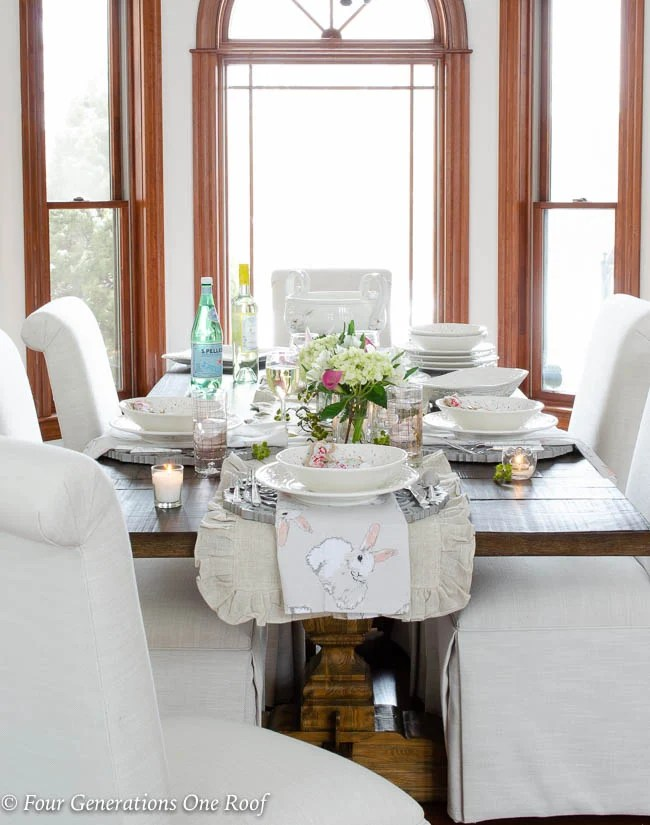 White Slipcovered Dining Room Chairs, Wood Farmhouse Table, Stained Trim,  White Tuscan Dishes