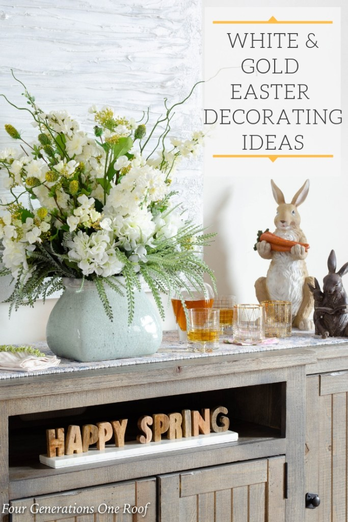 White + gold Easter Decorations, pastel blue vase with flowers, wood buffet table, Happy Spring Sign, wood Easter bunnies, decanter with liquor, gold rim glassware, white modern artwork