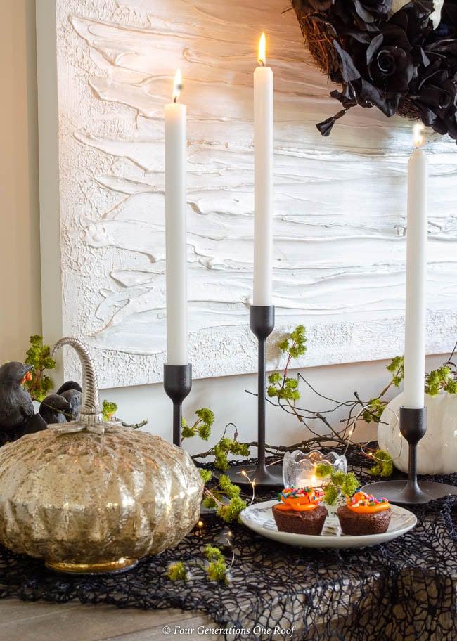 black candle stick holders + black and orange halloween cupcake table ideas