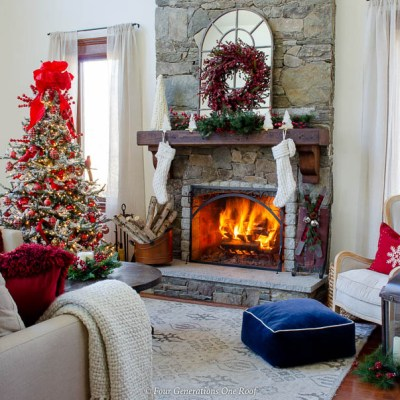 holiday brown wood mantel, white Christmas stockings, cranberry wreath, red christmas tree with red bow, fire in stone fireplace