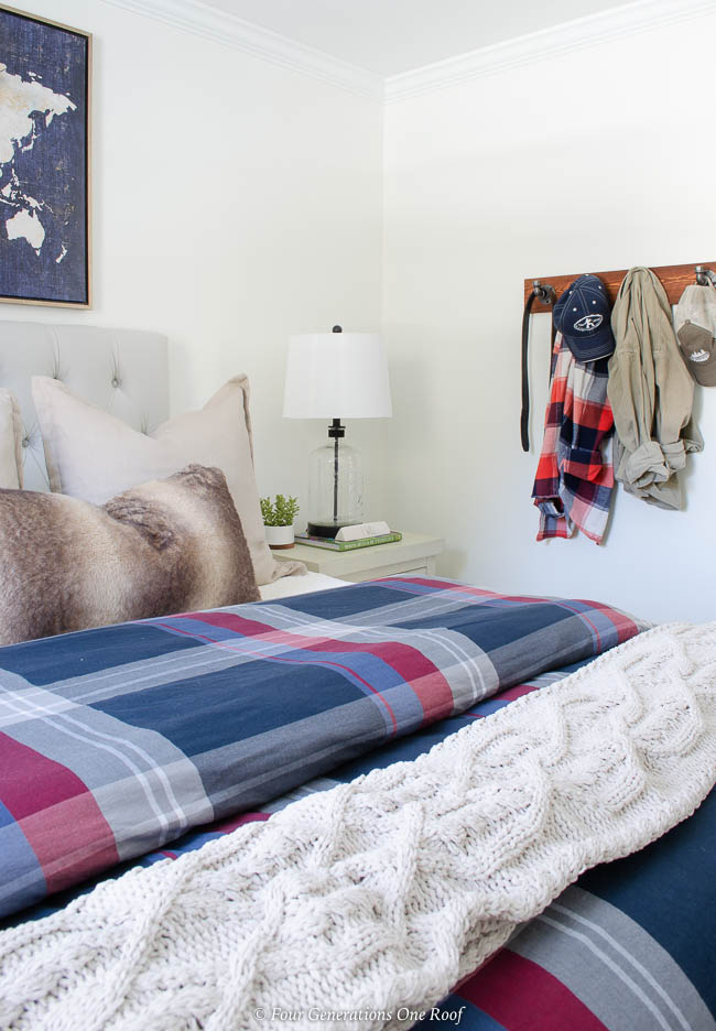 navy plaid duvet, cream cable knit throw, hanging coat rack, fur pillow