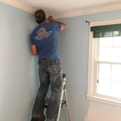 man applying white primer over blue walls in a bedroom