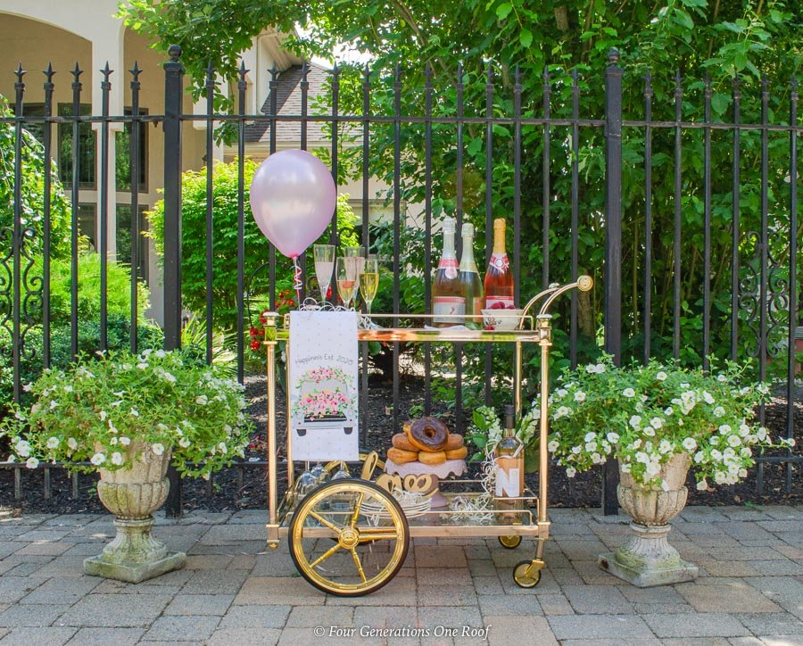 Backyard Bridal Shower Ideas on a budget with a gold bar cart champagne station on patio