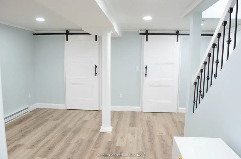 Masonite Livingston Interior Doors on black barn sliding hardware, harvest oak driftwood style flooring, blue walls
