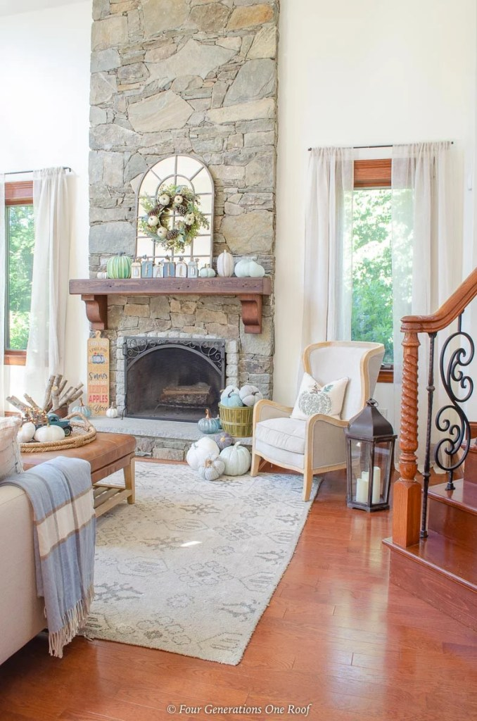 blue fall living room, blue pumpkins, arched mirror on mantel stone fireplace, blue fall wreath hanging on arched mirror