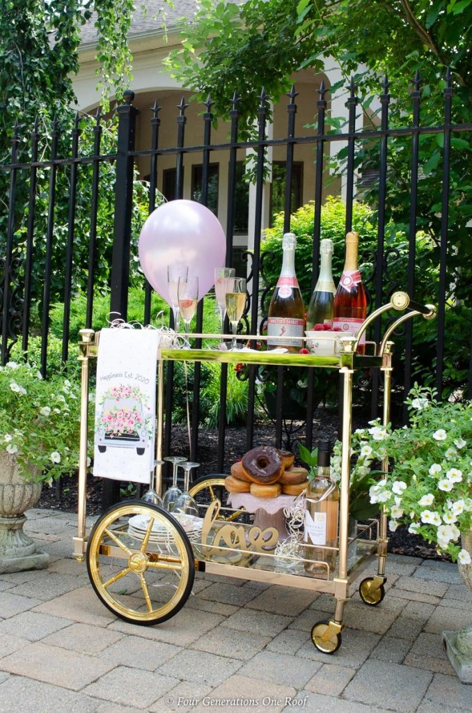 patio, rose gold bar cart, champagne, donut cake, pink balloon