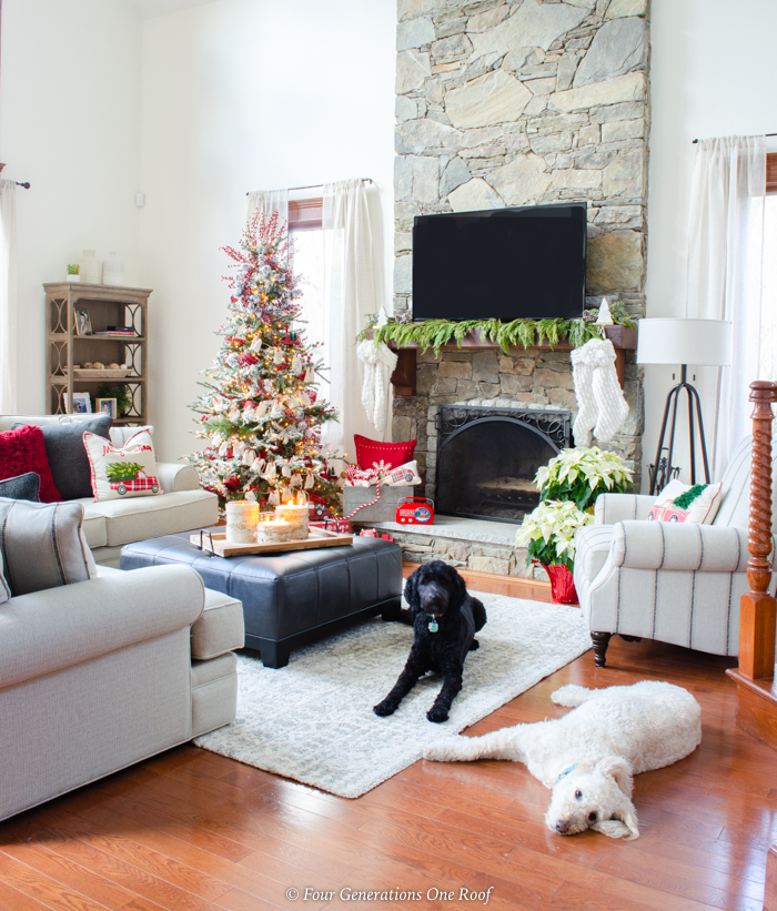 flocked christmas tree, goldendoodles, red christmas ornaments, red pillows, black ottoman coffee table, stone fireplace, wood mantel, tv over mantel