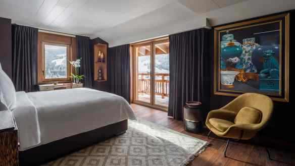 Suite des Aravis bed, accent chair, colourful painting, dark curtains on corner windows