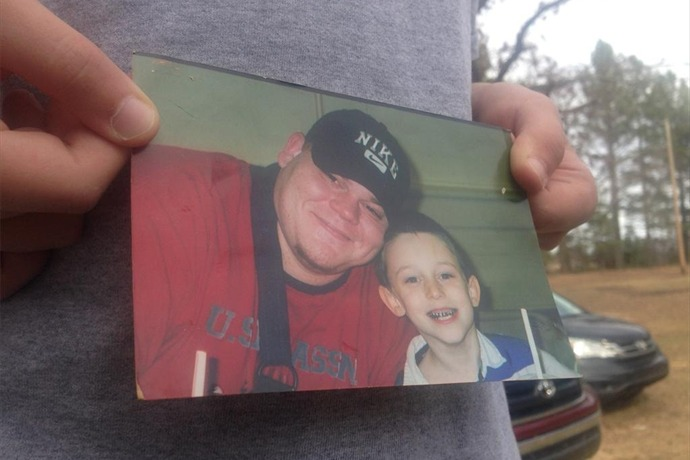 Barry Harmon's son holds a picture of he and his dad._-8826647914215616872