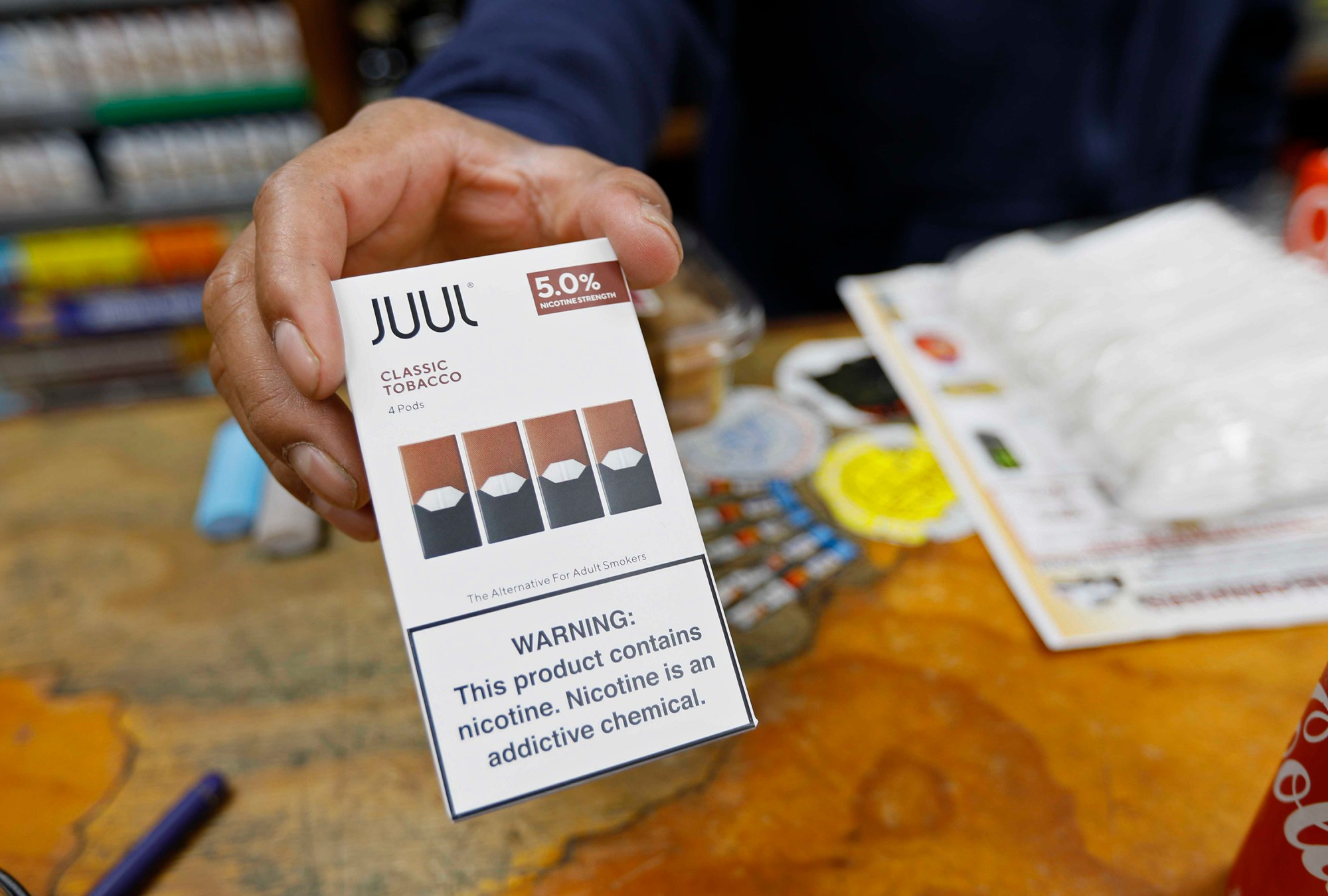File - In this June 17, 2019, file photo, a cashier displays a packet of tobacco-flavored Juul pods at a store in San Francisco. (AP Photo/Samantha Maldonado, File)
