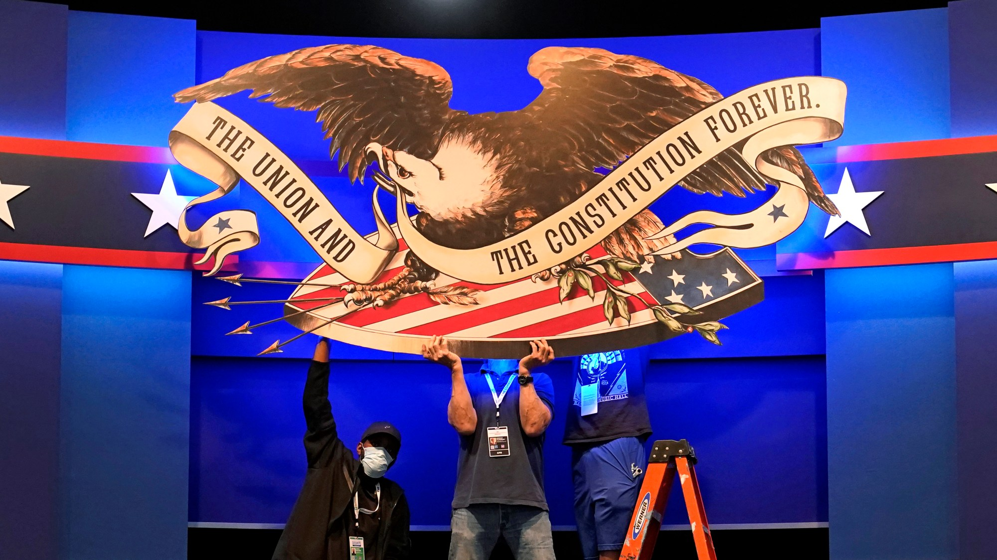 Workers adjust signage as preparations take place for the first Presidential debate in the Sheila and Eric Samson Pavilion, Monday, Sept. 28, 2020, in Cleveland. The first debate between President Donald Trump and Democratic presidential candidate, former Vice President Joe Biden is scheduled to take place Tuesday, Sept. 29. (AP Photo/Patrick Semansky)