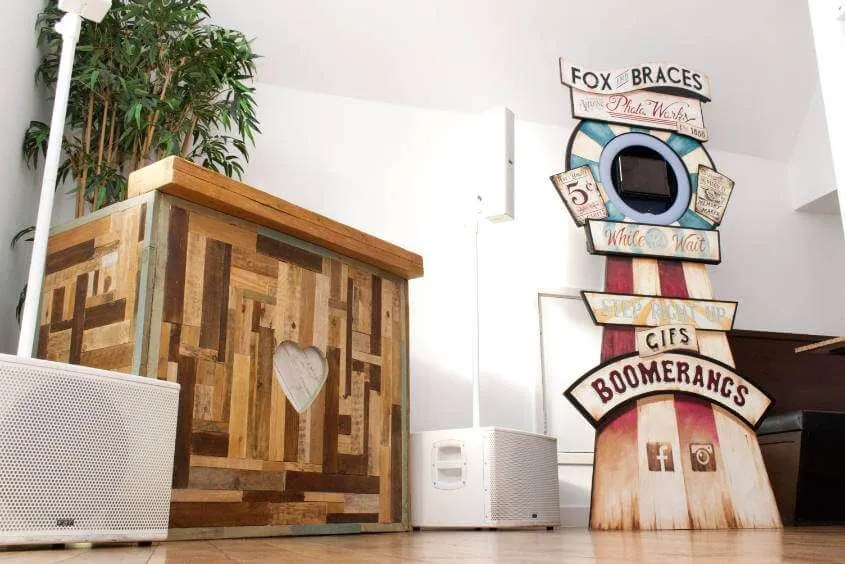 A rustic DJ booth and wooden selfie booth