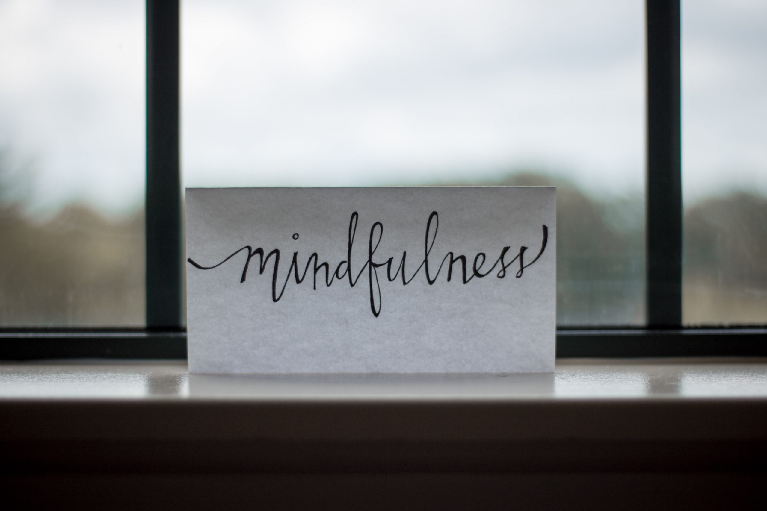 "The word ""mindfulness"" written in cursive on a white card with a foggy window pane in the background"