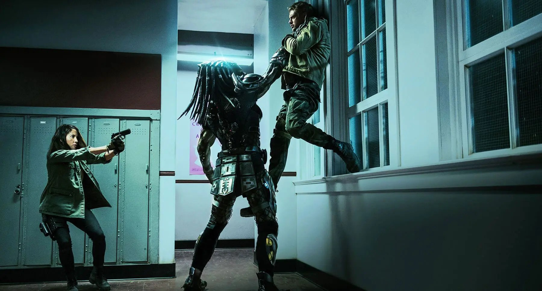 A Predator holding a woman by the throat against a wall