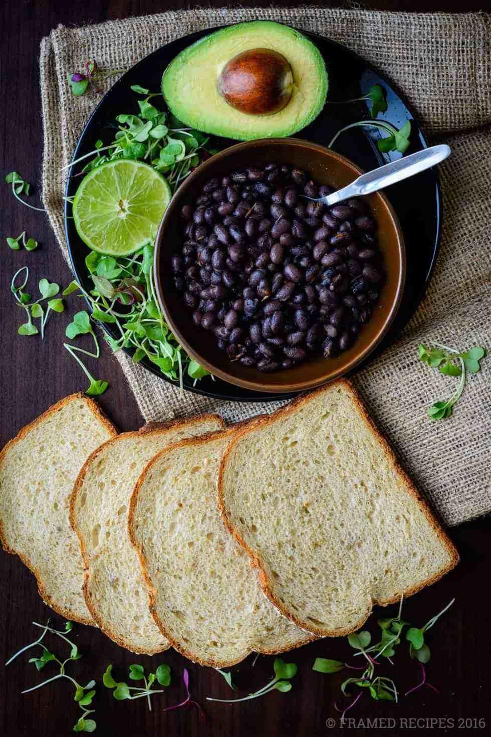 ingredients to prepare avocado toast -  bread slices, lemon, microgreens, whole avocado, black beans.