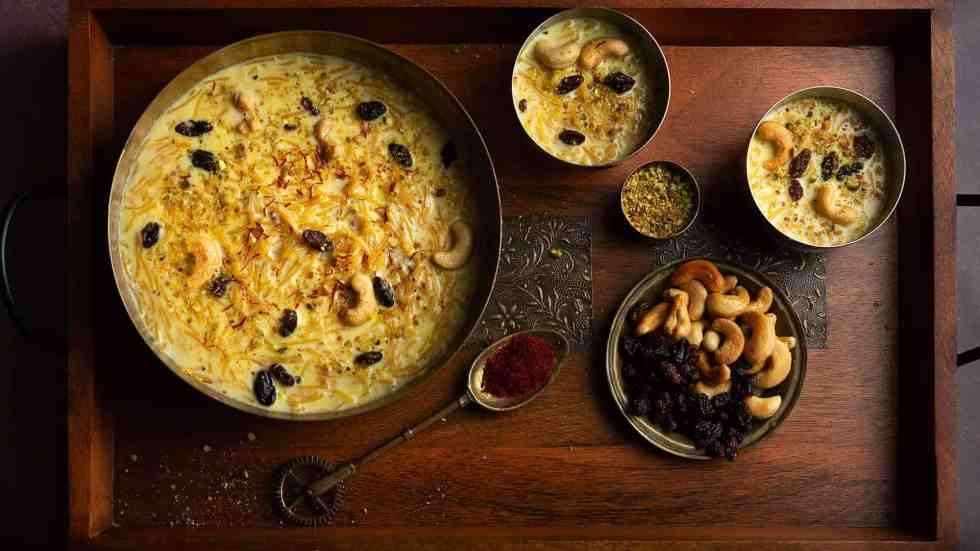 semiya payasam garnished with cashew nuts, raisins, and shown with smaller bowls of semiya payasam, nuts & saffron.
