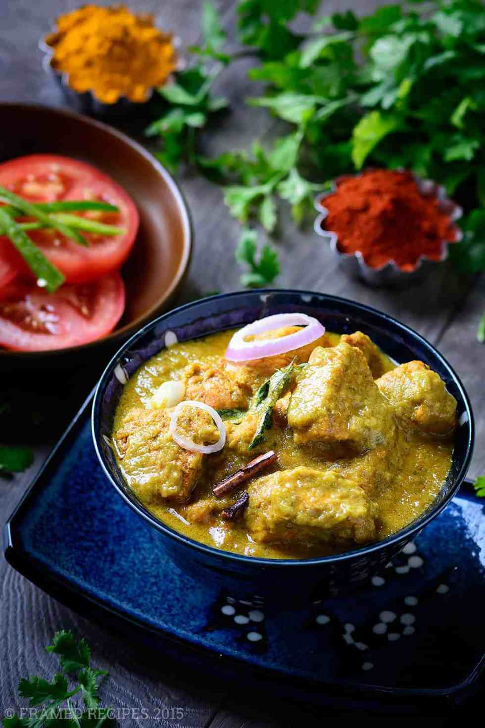 Cilantro_Chicken_Curry garnished with onion, served with tomato slices shown with red chilli powder and turmeric powder and cilantro in the background.