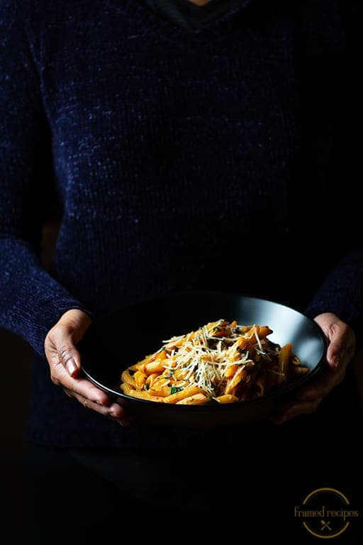 Cajun Spiced Spinach pasta in a black bowl held in hand