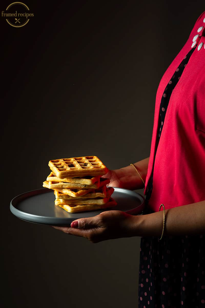 LADY HOLDING A PLATE OF YEASTED OATS WAFFLES