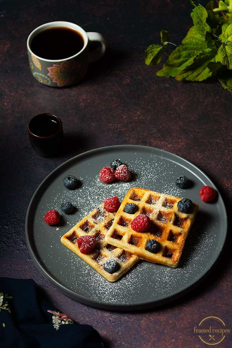 Yeasted_Oats_Waffles_MAPLE SYRUP_POURING_WITH_BERRIES aND POWDERED SUGAR