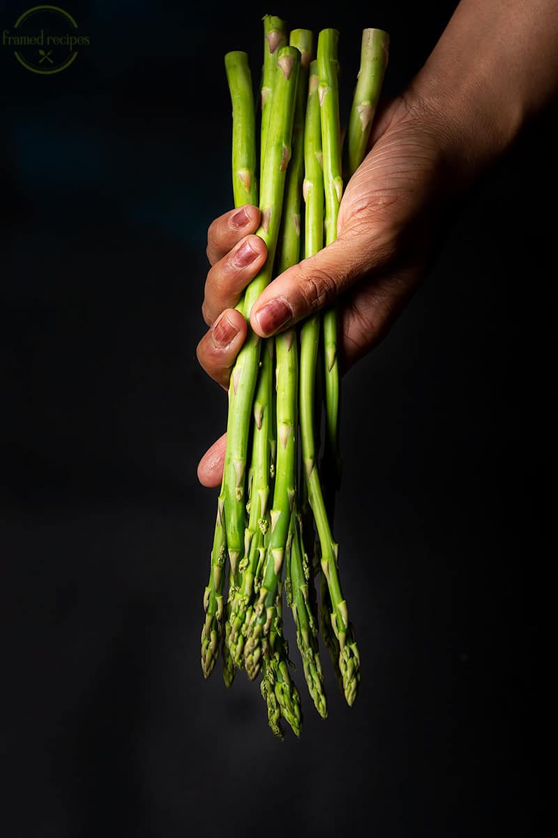 lady holding some fresh asparagus spears in hand.