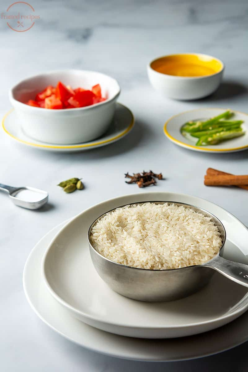 ingredients for making tomato bath or tomato rice - rice, cardamom, cloves, cinnamon, salt, green chillies, tomato and oil