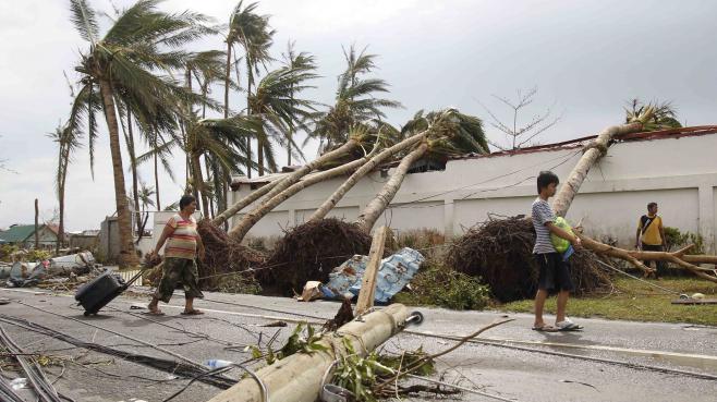 Des survivants du typhon Haiyan marchent dans la ville de Tacloban, le 9 novembre 2013, aux Philippines.