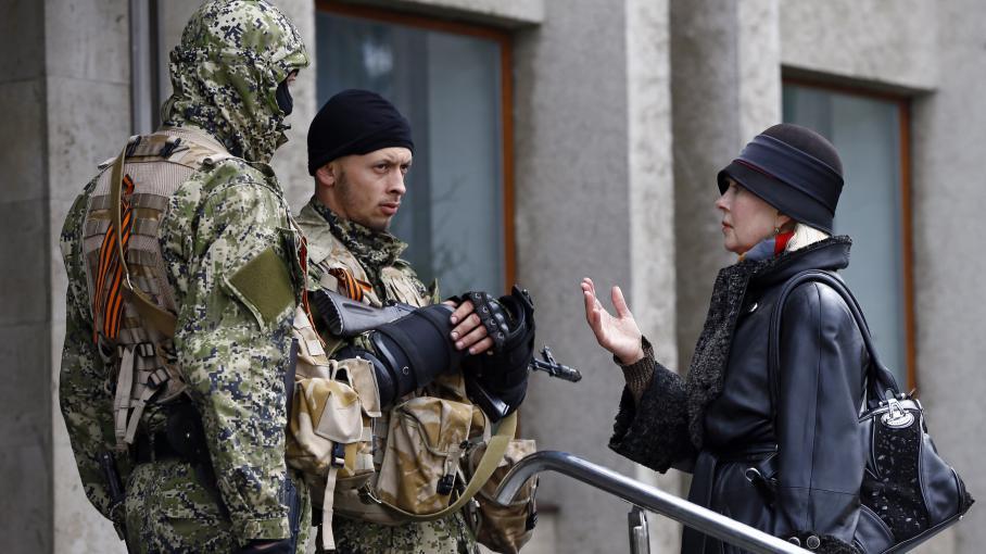 Une habitante discute avec des forces armées pro-russes devant la mairie de Sloviansk (Ukraine), le 14 avril 2014.