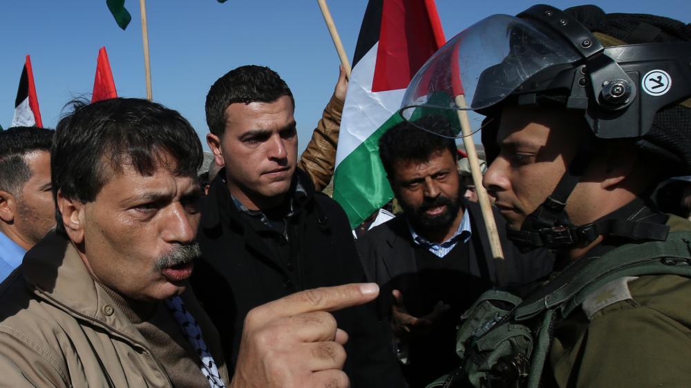 Le responsable palestinien Ziad Abou Eïn (G) interpelle des soldats israéliens quelques instants avant de trouver la mort, lors d'une manifestation à Turmus Ayya, en Cisjordanie, le 10 décembre 2014.