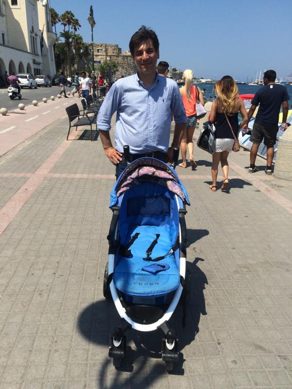 Nasser, touriste allemand en vacances à Kos (Grèce), le 20 août 2015, et la poussette qui lui sert à charrier les bouteilles d'eau qu'il offre aux migrants.