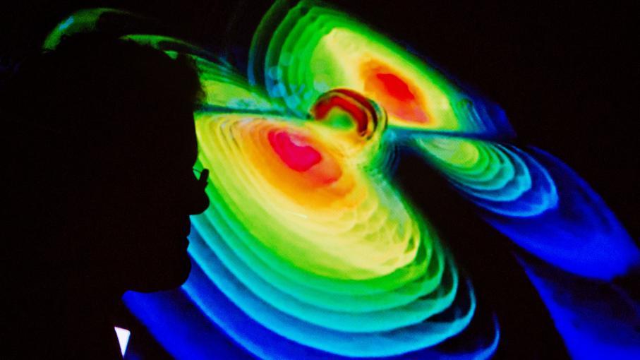 Le profil d\'un scientifique se découpe sur une représentation des ondes gravitationnelles durant une conférence de presse de l\'institut Max-Planck à l\'université Leibniz, à Hanovre en Allemagne, le 11 février 2016.
