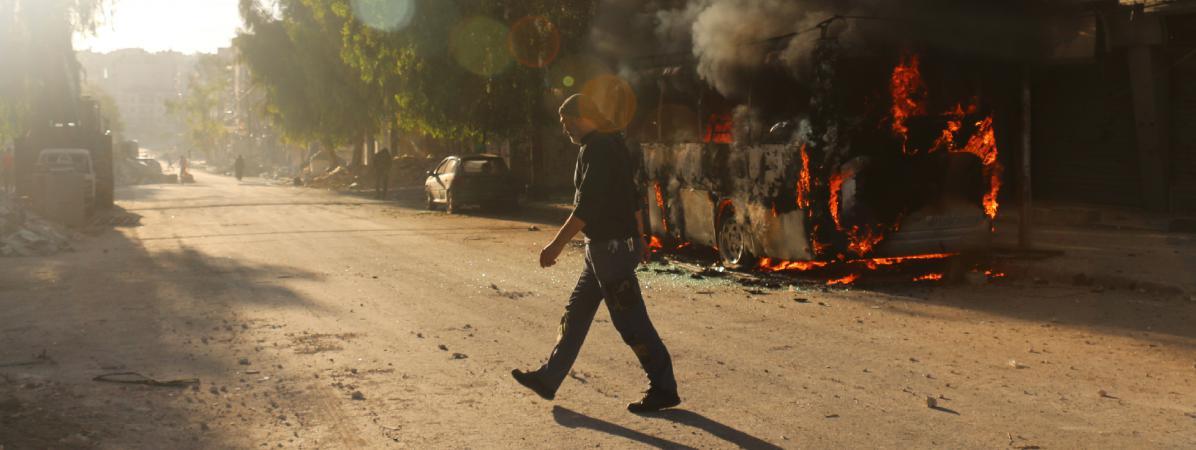 Un syrien marche devant un bus en feu à Alep en Syrie, le 25 septembre 2016.
