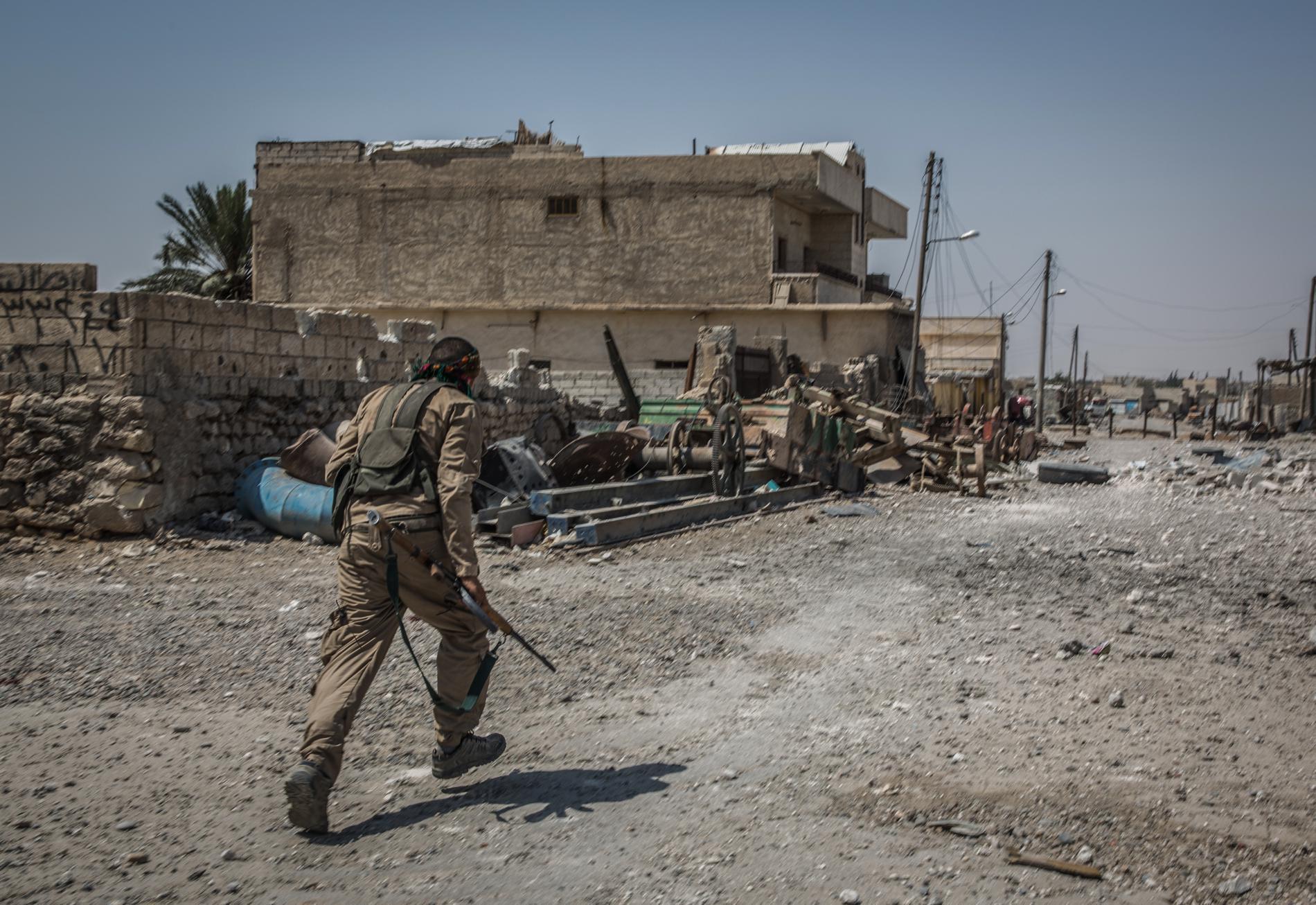 Un soldat des Forces démocratiques syriennes court dans une rue du quartier d\'Al-Sinaa, à Raqqa (Syrie) pour tenter d\'échapper à d\'éventuels tirs de snipers.