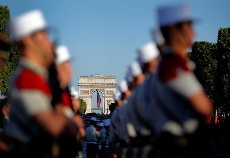 L\'Arc de Triomphe se profile derrière les rangs de soldats, le 14 juillet 2017.