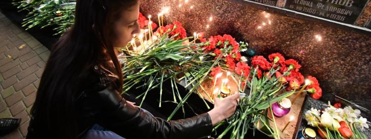 Une jeune femme allume une bougie près du monument en hommage aux victimes de la catastrophe, àSlavutych (Ukraine), le 26 avril 2019.