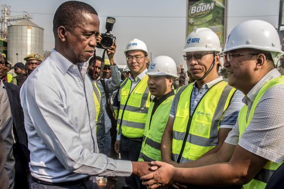 Le présidentzambien Edgar Lungu serrant la main de travailleurs chinois de l\'entreprise AVIC à Lusaka, en Zambie, le 15 septembre 2018.