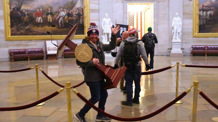 Un partisan de Donald Trump embarque un pupitre du Congrès, à Washington, mercredi 6 janvier 2021. (WIN MCNAMEE / GETTY IMAGES / AFP)