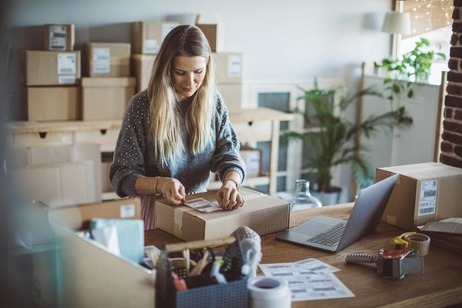 Working woman at online shop. She is wearing casual clothing and packaging goods for delivery