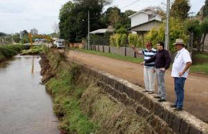 O morador Alcides Boelter, prefeito Cantelmo Neto e o diretor de Urbanismo Abel Vitto observam o primeiro trecho da dragagem do Lonqueador, que iniciou nesta semana