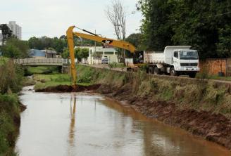 """Com um """"braço"""" adaptado que chega a 13 metros, a escavadeira e caminhões da Prefeitura fazem o serviço de desassoreamento do rio"""