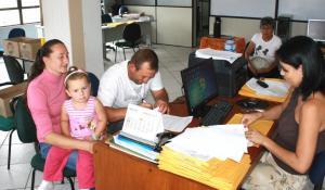 Franciele e Nelson Szupka, com a filha Letícia, assinam a documentação que será enviada à Caixa e Cooperhaf para análise: família está no primeiro grupo contemplado pelo programa