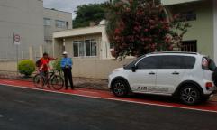 Ciclista conversa com agente de trânsito sobre veículo estacionado na ciclofaixa após o horário permitido