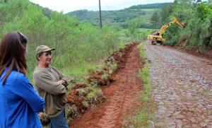 Secretária Daniela Celuppi e o agricultor Adão Varal observam a força tarefa na Linha Hobold