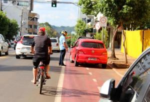 Enquanto agente do Debetran orienta veículo parado sobre a ciclofaixa, ciclista é obrigado a desviar e dividir espaço com os carros na rua