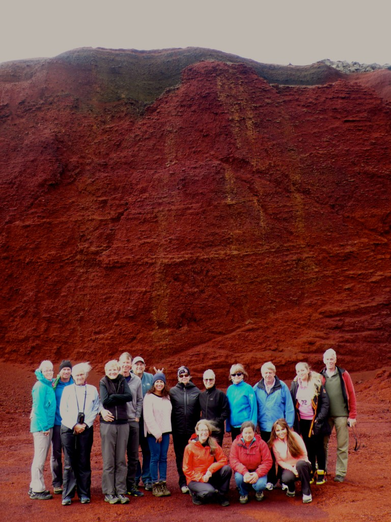 """Our group! The color of the lava is such a deep red.  The dark layers behind us is a layer of ash.  Jeff Bigman is giving me """"rabbit ears"""".  I'll have to get him back!"""