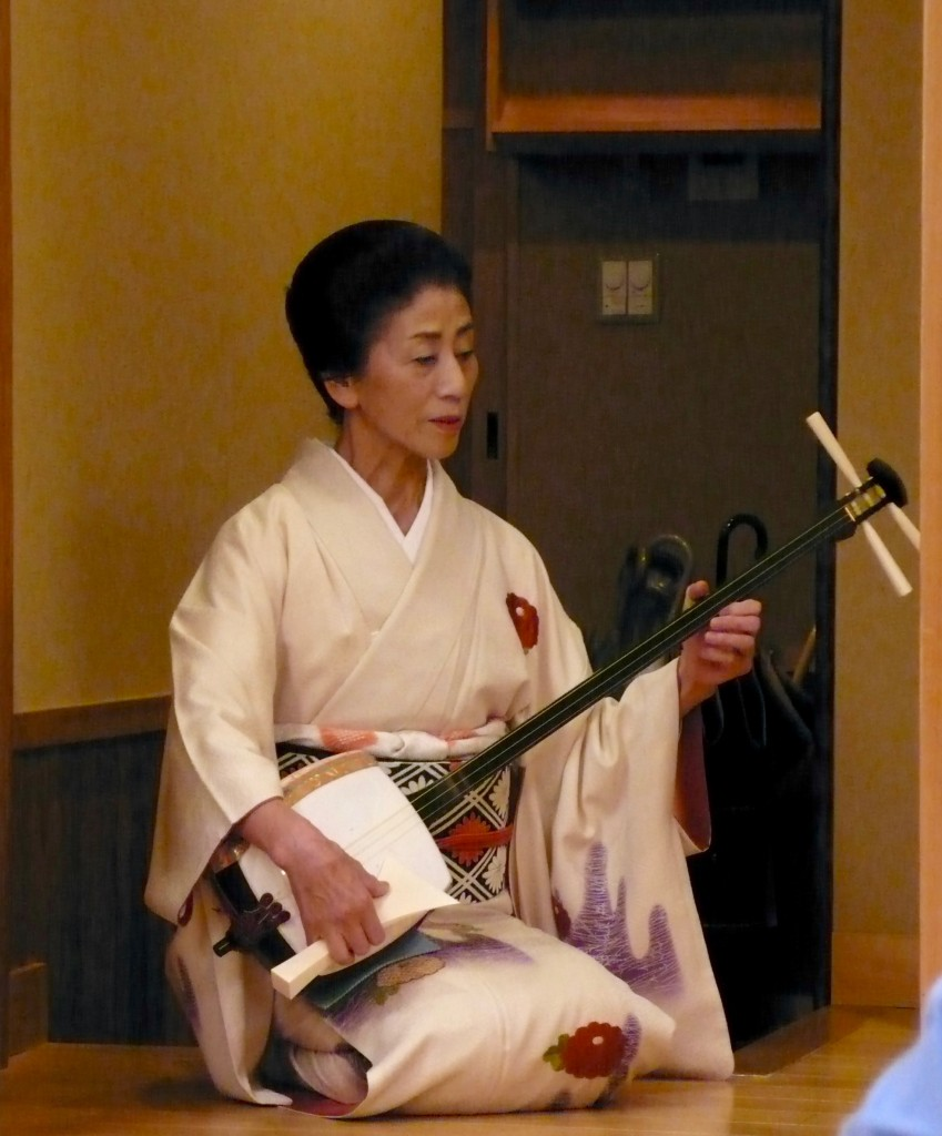 "We had dinner in an ancient tea house in Gion and a private performance. This is a shamisen player. She is an accomplished Geisha, though a respectful way to refer to her is GEIKO because she has devoted her entire life to be being a Geisha (since she was 15 years old).  Geisha literally means, ""a person of the arts"", Geiko literally means ""A woman of the arts""  Geiko cannot get married.  They symbolize the high culture of Japan.  They are female entertainers (this woman played and sang for us)  who act as hostess and whose skills include performing various arts such as classical Japanese music, dance, games and conversation.  She later went around to our table and spoke to us.  She was lovely in all ways."