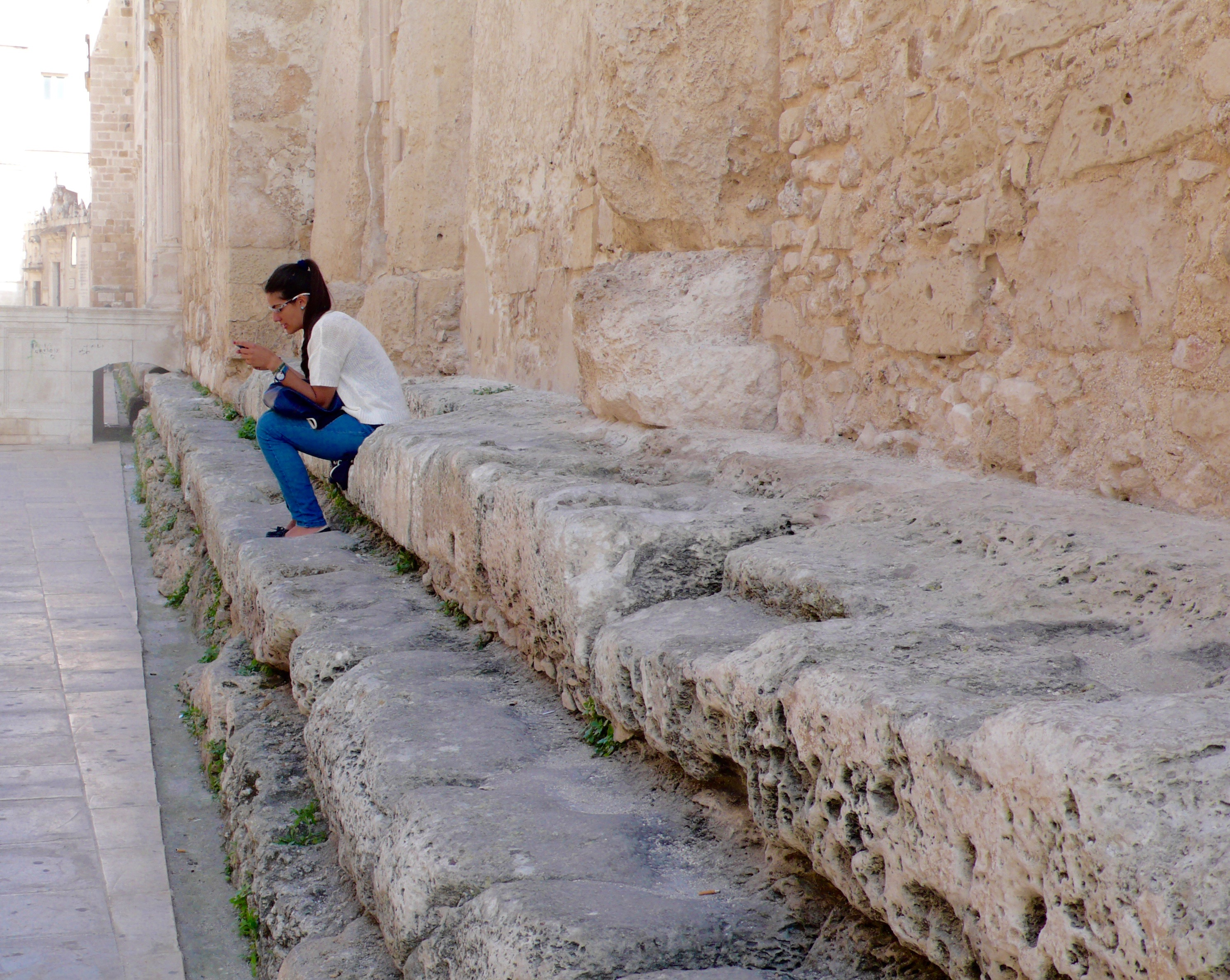 Sicilian girl sitting on the steps dating back to the the ancient Greek temple-turned Catholic Cathedral