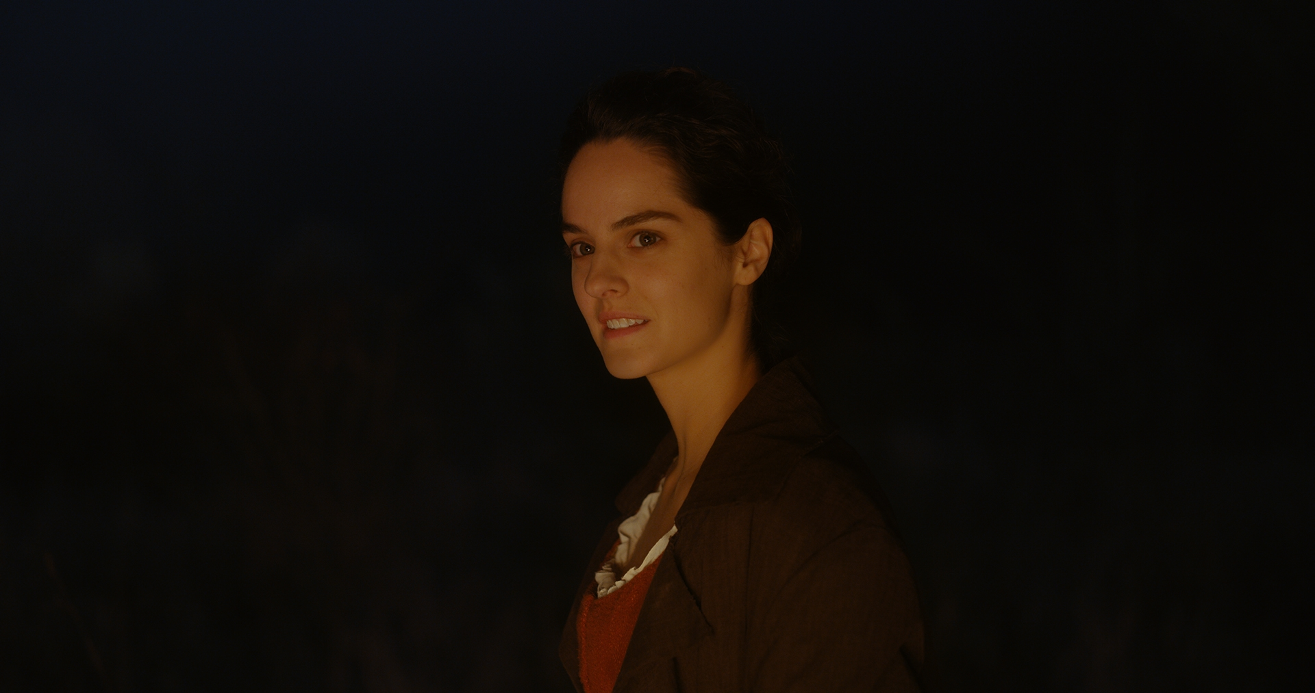 Noémie Merlant as Marianne by the bonfire in Portrait of a Lady on Fire