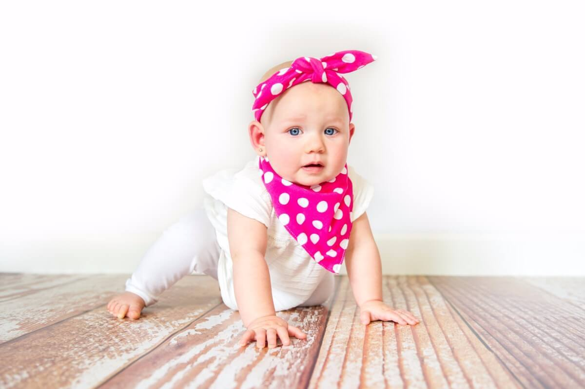 Toddler with hot pink headband and bib