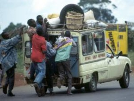 Touts hanging on a matatu Kenya